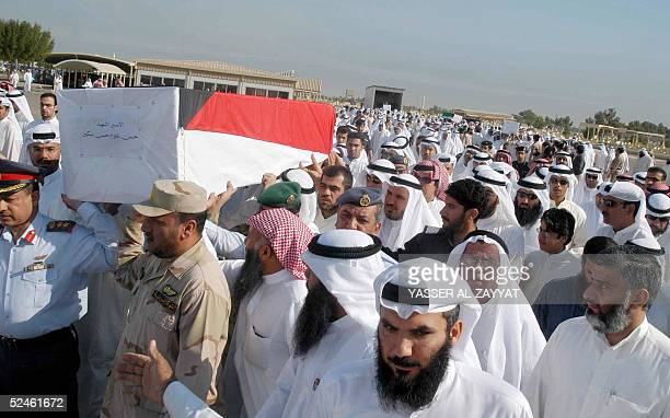 Reletives carry the coffin of one of seven Kuwaitis found recently in a mass grave in Iraq during his funeral 21 March 2005 at a cemetary in Kuwait...