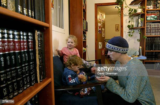 Relgious Hebrew books line the walls as Shira Hendler tends to her young children 18monthold Yishai and 3yearold Hilla in their caravan home December...