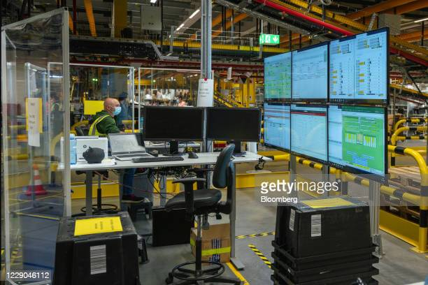 Reliability Maintenance Engineering Technician works between perspex screens to assist social distancing while monitoring workflow inside Amazon.com...