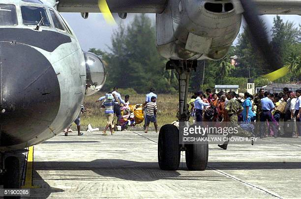 Relief goods are unloaded from an Indian army plane while residents wait to board the plane to be evacuated in Campbell Bay island an island of...