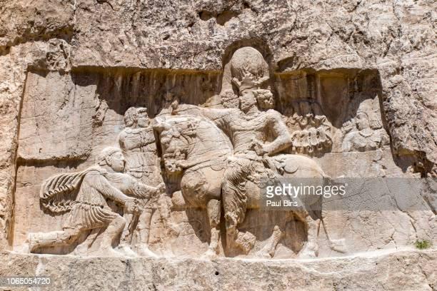 relief of triumph of shapur i over roman emperors valerian and philip arab, naqsh-e rustam, persepolis, iran - iraq stock pictures, royalty-free photos & images