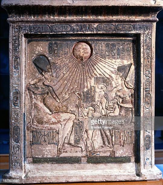 A relief on a stela showing an intimate family scene Akhenaten Nefertiti and their three daughters are seated beneath the rays of Aten the sun Egypt...