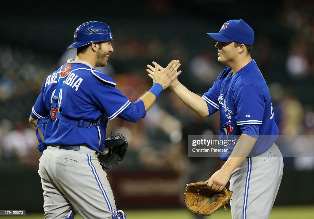 Relief pitcher Aaron Loup #62 of the Toronto Blue Jays celebrates with catcher catcher J.P. Arencibia #9 after defeating the Arizona Diamondbacks 10-4 in the interleague MLB game at Chase Field on September 3, 2013 in Phoenix, Arizona.