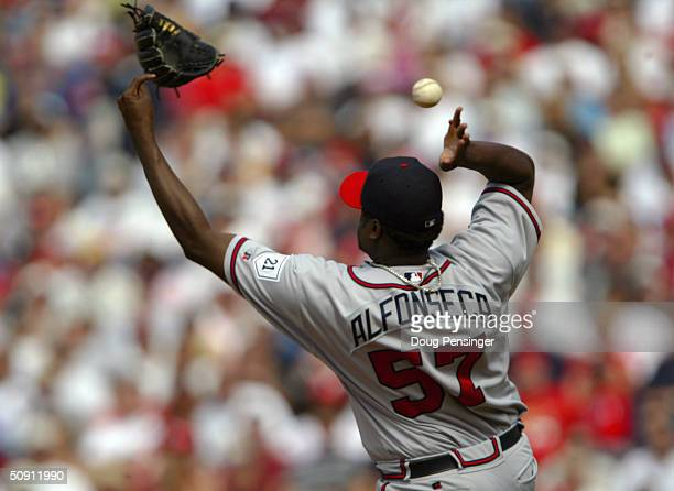 Relief pitcher Antonio Alfonseca of the Atlanta Braves looses his glove as he knocks down a sharpley hit grounder and throws out Tomas Perez of the...