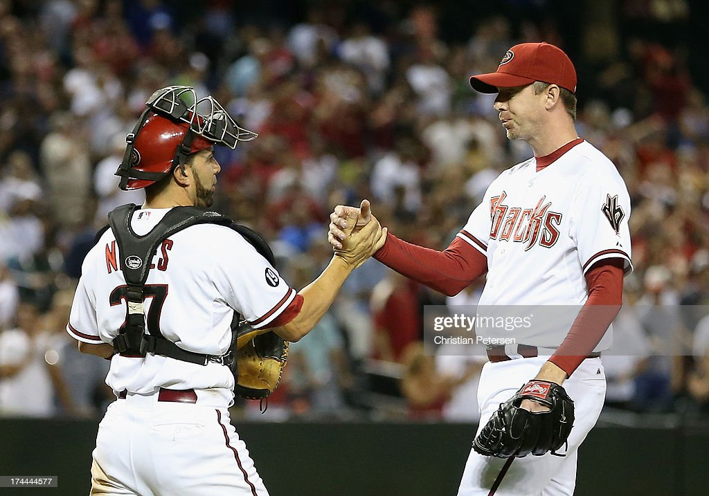 Relief pitcher Brad Ziegler #29 of the Arizona Diamondbacks celebrates with catcher Wil Nieves #27 after defeating the Chicago Cubs in the MLB game at Chase Field on July 25, 2013 in Phoenix, Arizona. The Diamondbacks defeated the Cubs 3-1.