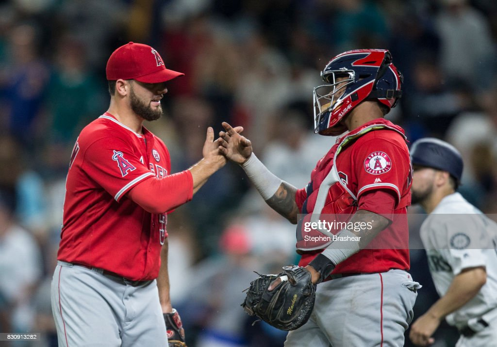 Relief pitcher Cam Bedrosian #32, left, of the Los Angeles Angels of Anaheim and catcher Martin Maldonado #12 of the Los Angeles Angels of Anaheim celebrate after a game against the Seattle Mariners at Safeco Field on August 12, 2017 in Seattle, Washington. The Angels won the game 6-3 and Bedrosian got the save.