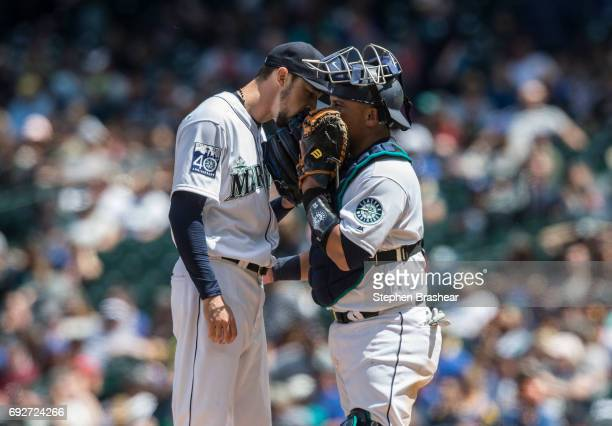Relief pitcher Casey Lawrence of the Seattle Mariners and catcher Carlos Ruiz meet at the pitcher's mound during a game against the Colorado Rockies...