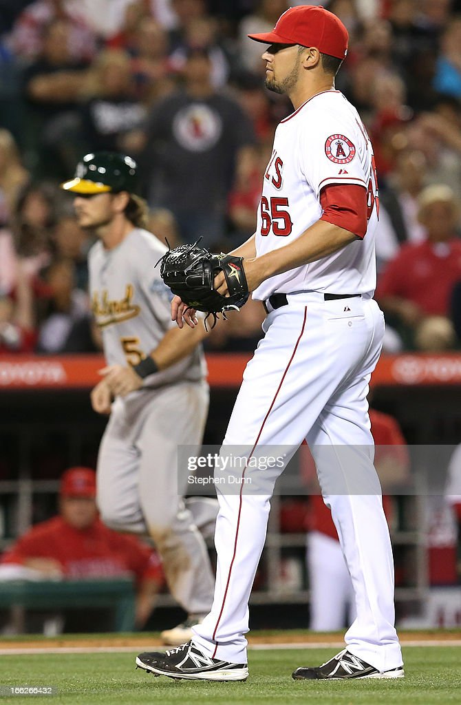 Relief pitcher Dane De La Rosa #65 of the Los Angeles Angels of Anaheim reacts after walking in John Jaso #5 of the Oakland Athletics in the sixth inning at Angel Stadium of Anaheim on April 10, 2013 in Anaheim, California.