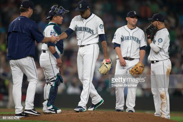 Relief pitcher Edwin Diaz center of the Seattle Mariners is pulled by manager Scott Servais far left during a meeting at the pitcher's mound with...