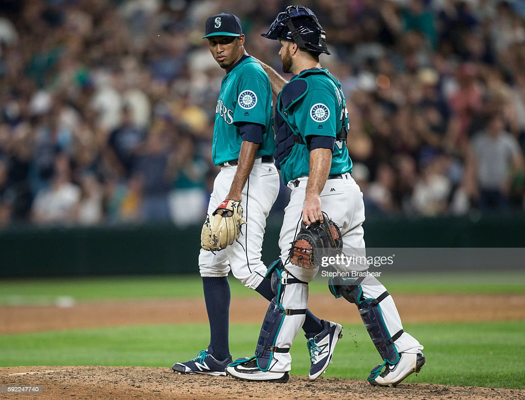 Relief pitcher Edwin Diaz #39, left, of the Seattle Mariners and catcher Chris Iannetta #33 of the Seattle Mariners walk off the field after game against the Milwaukee Brewers at Safeco Field on August 19, 2016 in Seattle, Washington. The Mariners won the game 7-6 and Diaz got the save.