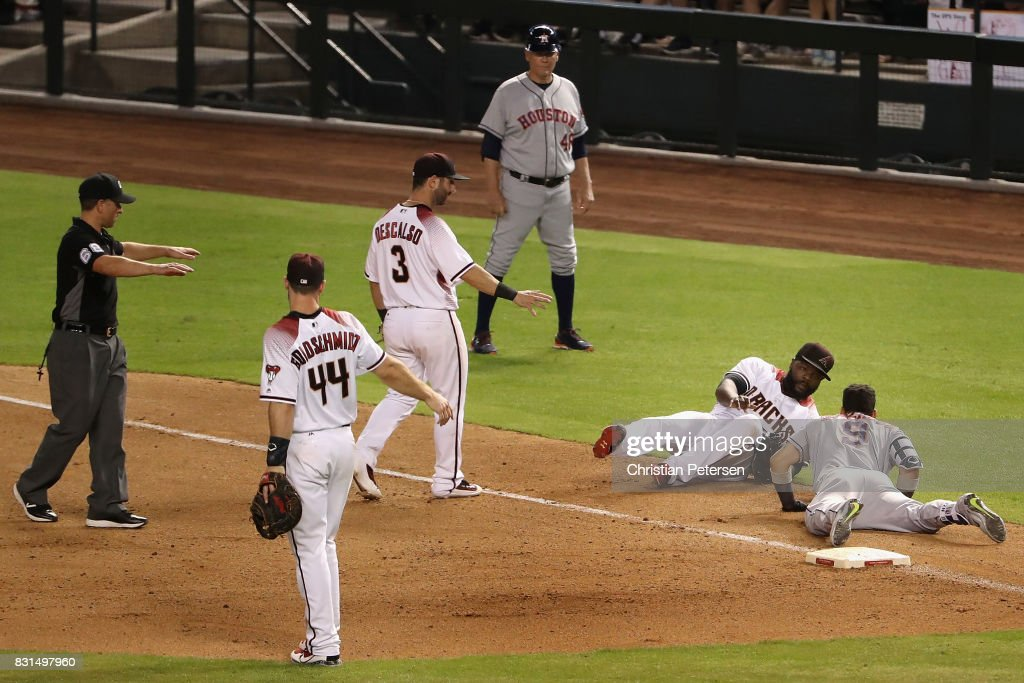 Relief pitcher Fernando Rodney #56 of the Arizona Diamondbacks falls over Marwin Gonzalez #9 of the Houston Astros as he attempted to tag him out on an infield single during the ninth inning of the MLB game at Chase Field on August 14, 2017 in Phoenix, Arizona. The Diamondbacks defeated the Astros 2-0.