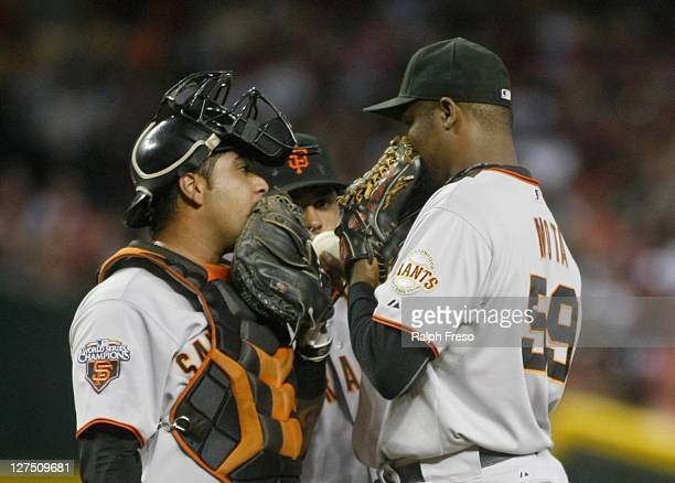 Relief pitcher Guillermo Mota of the San Francisco Giants and catcher Hector Sanchez have a hidden conversation on the mound during a timeout against...