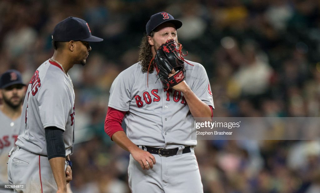Relief pitcher Heath Hembree #37 of the Boston Red Sox reacts before getting pulled from a game against the Seattle Mariners in the seventh inning at Safeco Field on July 25, 2017 in Seattle, Washington. The Mariners won the game 6-5 in 13 innings. At left is shortstop Xander Bogaerts #2 of the Boston Red Sox. The Mariners won the game 6-5 in thirteen innnings.