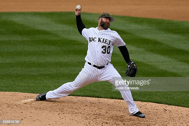 Relief pitcher Jason Motte of the Colorado Rockies delivers to home plate during the seventh inning against the Cincinnati Reds at Coors Field on May...