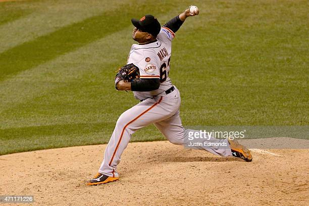 Relief pitcher Jean Machi of the San Francisco Giants delivers to home plate during the 11th inning against the Colorado Rockies at Coors Field on...