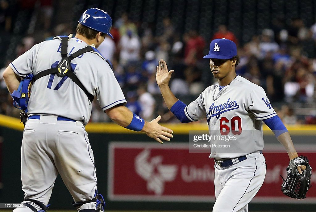 Relief pitcher Jose Dominguez #60 of the Los Angeles Dodgers celebrates with catcher A.J. Ellis #17 after defeating the Arizona Diamondbacks in the MLB game at Chase Field on July 8, 2013 in Phoenix, Arizona. The Dodgers defeated the Diamondbacks 6-1.
