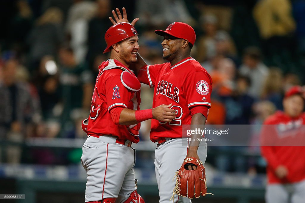Relief pitcher Jose Valdez #32 (R) of the Los Angeles Angels of Anaheim is congratulated by catcher Carlos Perez #58 after beating the Seattle Mariners 10-3 at Safeco Field on September 3, 2016 in Seattle, Washington.