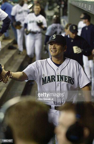Relief pitcher Kazuhiro Sasaki of the Seattle Mariners is congratulated by teammates in the dugout after getting the victory over the Texas Rangers...
