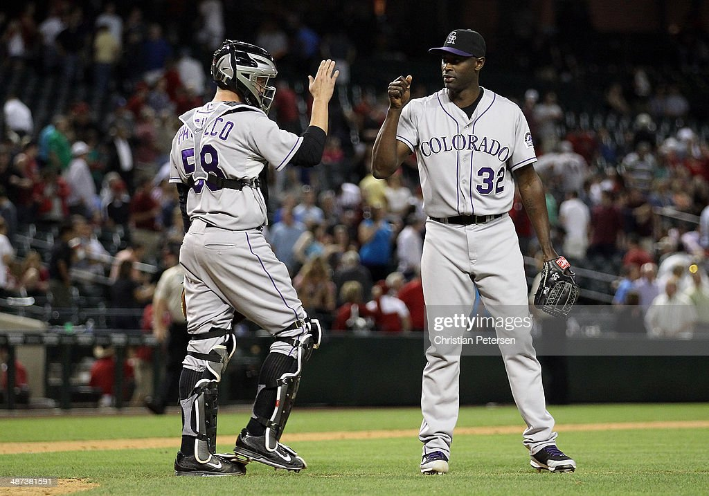 Relief pitcher LaTroy Hawkins #32 of the Colorado Rockies high-fives catcher Jordan Pacheco #58 after defeating the Arizona Diamondbacks in the MLB game at Chase Field on April 29, 2014 in Phoenix, Arizona. The Rockies defeated the Diamondbacks 5-4.