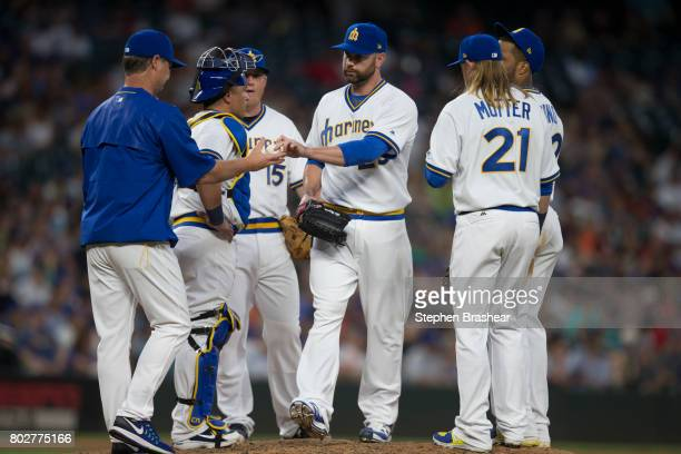 Relief pitcher Marc Rzepczynski third from right is pulled by Seattle Mariners manager Scott Servais far left during a meeting at the pitcher's mound...