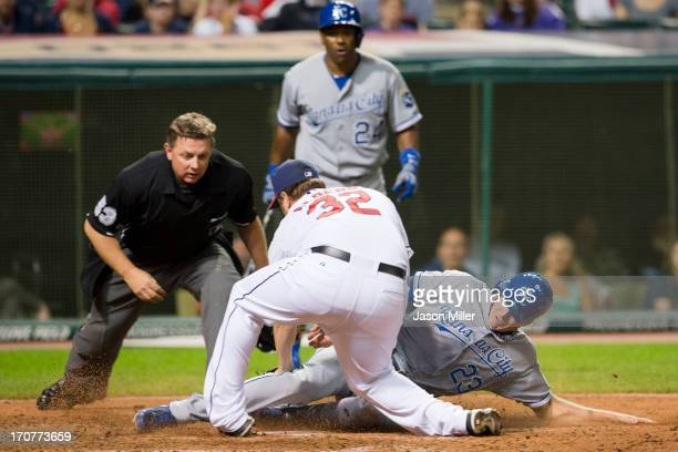 Relief pitcher Matt Albers of the Cleveland Indians tries to tag out Elliot Johnson of the Kansas City Royals who is safe at home during the ninth...