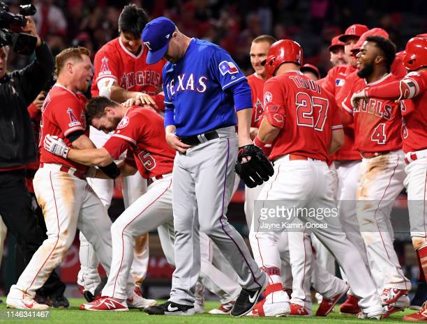 Relief pitcher Shawn Kelley of the Texas Rangers walks off the field as the Los Angeles Angels of Anaheim celebrate a walk off pinch hit single by...