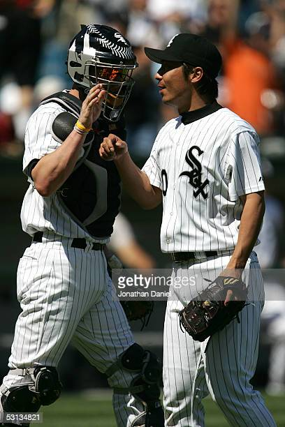 Relief pitcher Shingo Takatsu of the Chicago White Sox is congratulated by teammate Chris Widger after pitching against the Kansas City Royals in the...
