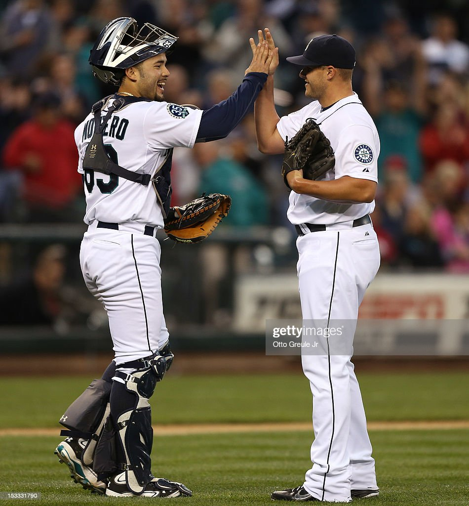 Relief pitcher Stephen Pryor #46 of the Seattle Mariners is congratulated by catcher Jesus Montero #63 after defeating the Los Angeles Angels of Anaheim 12-0 at Safeco Field on October 3, 2012 in Seattle, Washington.
