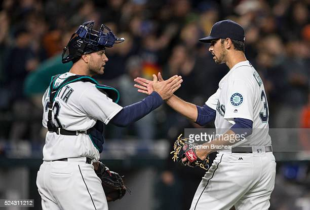 Relief pitcher Steve Cishek of the Seattle Mariners is congratulated by catcher Chris Iannetta after earning a save in a game against the Houston...