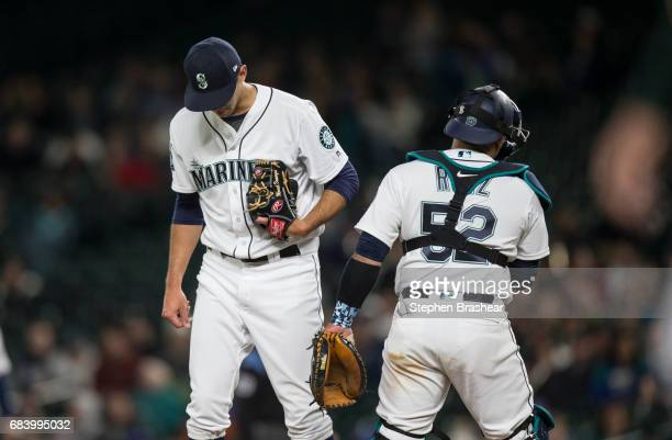 Relief pitcher Steve Cishek of the Seattle Mariners meets at the mound with catcher Carlos Ruiz of the Seattle Mariners during the ninth inning of a...