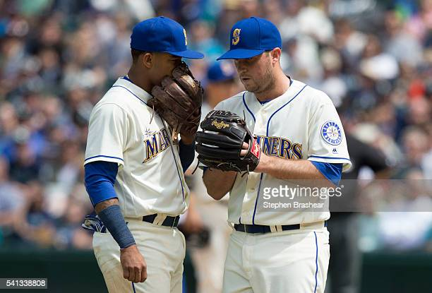 Relief pitcher Steve Johnson right of the Seattle Mariners meets with shortstop Ketel Marte of the Seattle Mariners during a game against the Texas...