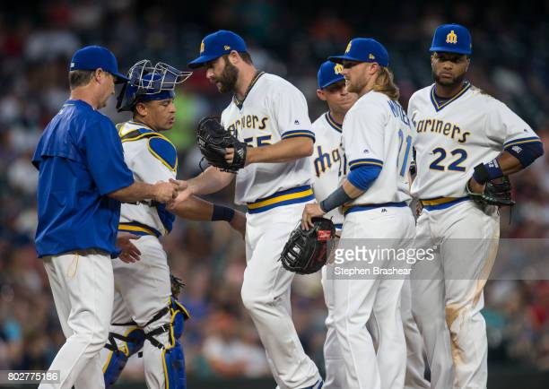 Relief pitcher Tony Zych third from left is pulled by Seattle Mariners manager Scott Servais far left during a meeting at the pitcher's mound...