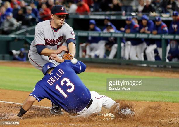Relief pitcher Tyler Duffey of the Minnesota Twins is unable to catch the throw from catcher Chris Gimenez allowing Joey Gallo of the Texas Rangers...