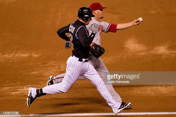 Relief pitcher Wade Miley of the Arizona Diamondbacks shows the ball to the umpire after beating Tyler Colvin of the Colorado Rockies to first base...