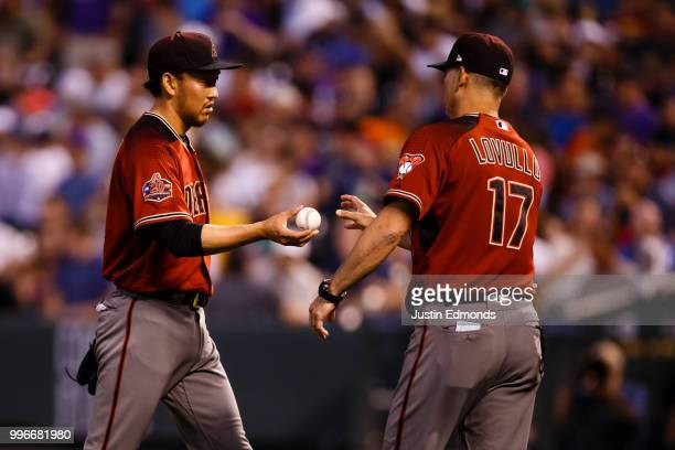 Relief pitcher Yoshihisa Hirano of the Arizona Diamondbacks hands the baseball to Manager Torey Lovullo during the fourth inning against the Colorado...