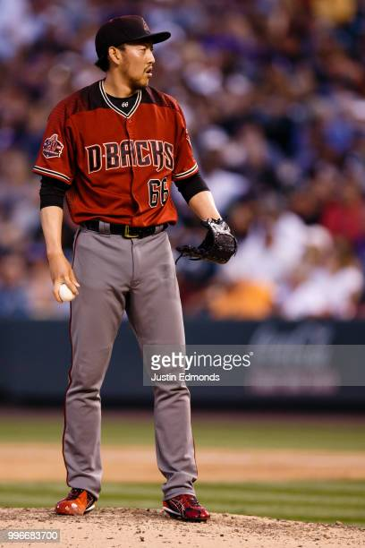Relief pitcher Yoshihisa Hirano of the Arizona Diamondbacks waits for the sign during the fourth inning against the Colorado Rockies at Coors Field...