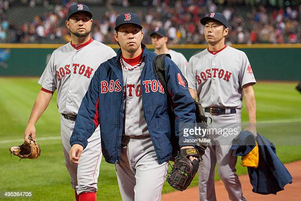 Relief pitchers Edward Mujica Junichi Tazawa and Koji Uehara of the Boston Red Sox walk in from the right field bullpen after the Cleveland Indians...