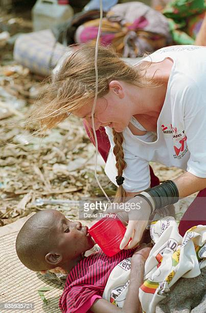A relief worker gives a sick refugee child fresh water