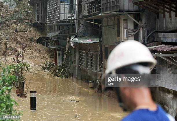 A relief worker stands at the scene of a mud slide and flooding in New Taipei City on August 2 2012 Typhoon Saola pounded Taiwan with fierce winds...