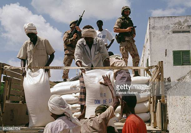 CARE relief workers distribute the first military convoy of humanitarian aid in Mogadishu after 28000 United States Marines were sent during...