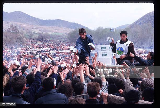 Relief workers hand supplies to refugees April 1 1999 in Macedonia Thousands of Kosovar Albanians fled the violence in Serbia and arrived at Blace a...