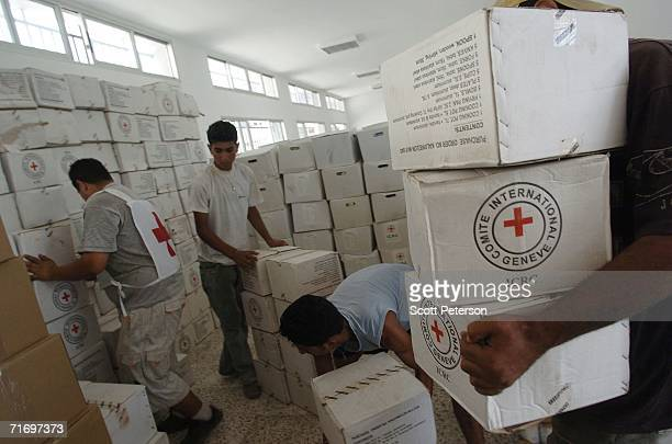 Relief workers of the International Committee of the Red Cross carry kitchen sets and food August 22 200 in the village of AlQlaileh Lebanon Led by...