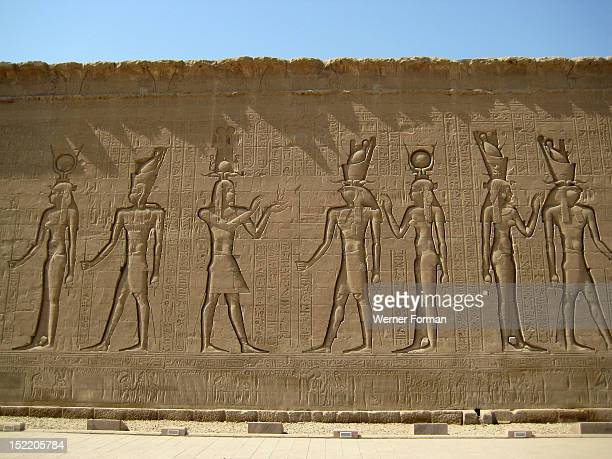 Reliefs on the outer back walls of the temple complex depicting a procession of gods and goddesses including Horus and Isis They are holding the ankh...