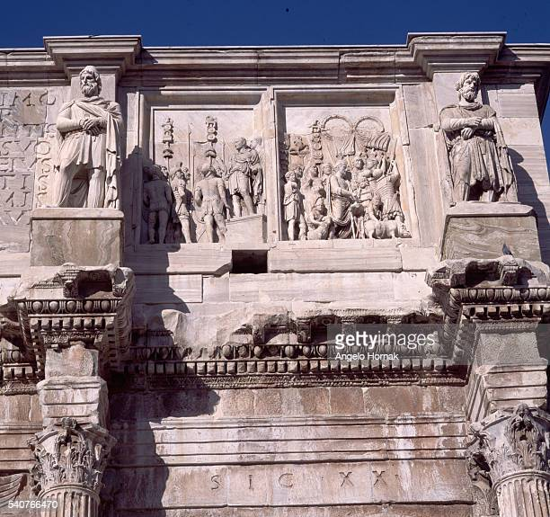 Reliefs on two panels between Dacian captives depicts Trajan addressing his troops and a sacrificial ceremony on the south face entablature on the...