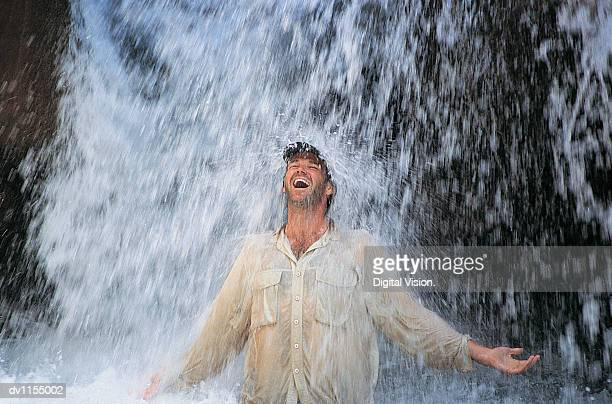 relieved man standing below a waterfall with his arms out - rafraîchissement photos et images de collection