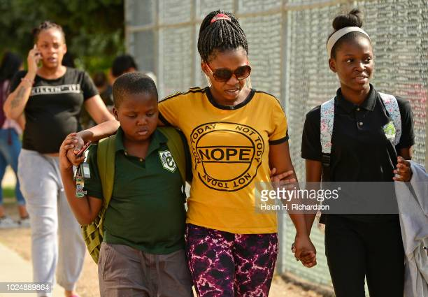 Relieved Odilla Irakunda, middle, holds the hands of her daughter Nori and son Stephan after the two were released from Cole Middle school after it...