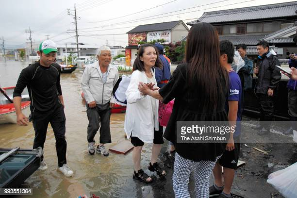 Relieved people are seen after rescued as the Mabicho area is submerged after Odagawa River banks collapse due to heavy rain on July 7 2018 in...