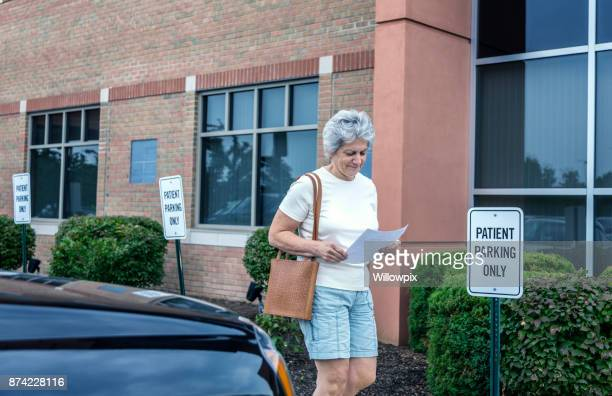 Relieved Senior Adult Woman Medical Patient Leaving Doctor's Office