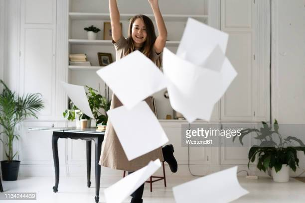 relieved young woman throwing blank sheets of paper in the air - professional occupation photos et images de collection