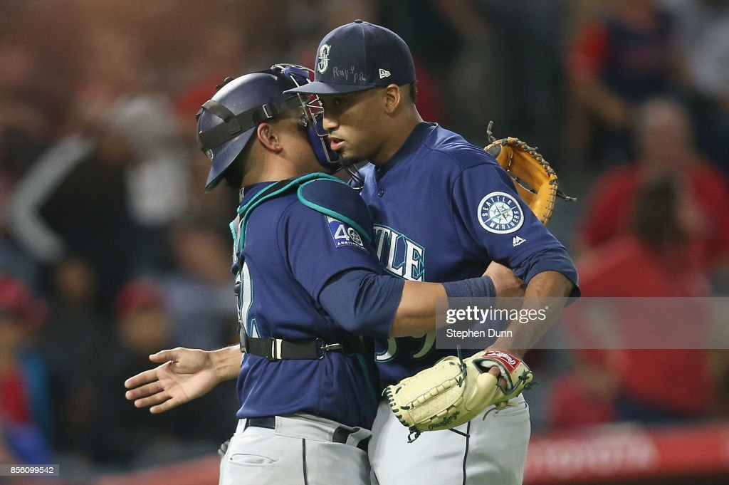 Reliever Edwin Diaz #39 and catcher Carlos Ruiz #52 of the Seattle Mariners celebrate after Diaz pitched the ninth inning to pick up the save against the Los Angeles Angels of Anaheim on September 30, 2017 at Angel Stadium of Anaheim in Anaheim, California. The Mariners won 6-4.
